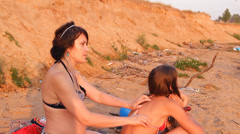 The mother and a girl on the beach, a woman makes massage Stock Footage