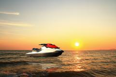 Jetski above the water at sunset Stock Photos