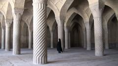 Classic mosque in Iran, woman in chador walks through pillars Stock Footage