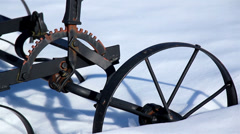 Wheel of an old agri tool stuck on the snow Stock Footage