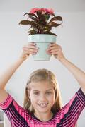 Portrait of girl (8-9) holding flower pot Stock Photos
