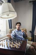Portrait of young man playing chess Stock Photos