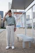 Senior man standing and saluting at bus stop Stock Photos