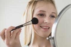 Stock Photo of Girl (14-15) applying make up