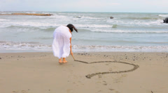 Beautiful woman painting heart on sand Stock Footage