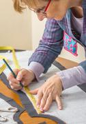 dressmaker drawing tailor pattern on the table - stock photo