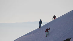 Skiers climbing up ridge or spine Stock Footage