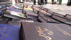 Pedestrians walk past Qurans and other books for sale on streets of Tabriz Iran Stock Footage