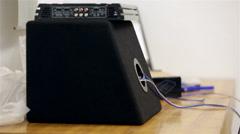 Amplifier and car subwoofer on workshop desk - stock footage
