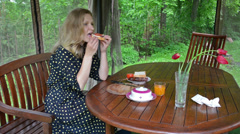 Blond woman in spotted dress eat sandwich for breakfast in bower Stock Footage
