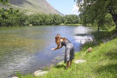 The young girl meditates on the shore of a mountain lake Stock Photos