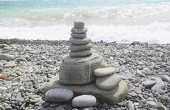 the pyramid of stones is on the beach - stock photo