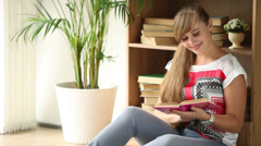 Beautiful girl sitting on floor by bookcase reading book looking at camera Stock Footage