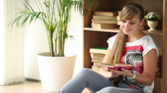 Charming girl sitting on floor beside bookcase reading book looking at camera Stock Footage