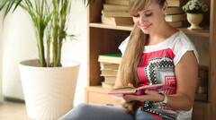 Cute girl siting on floor by bookcase reading book looking at camera and smiling Stock Footage