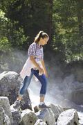 Young girl goes on the rocks by a mountain river Stock Photos