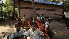 Young boys and girl sit around camera in rural village school in Kerela, India Stock Footage