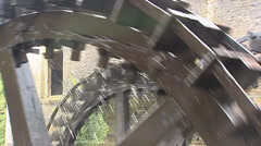 Traditional wooden water wheels turning in front of brick wall of saw mill Stock Footage