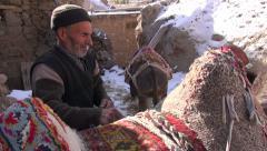 Rural Iran, man saddles up his donkey in small mountain village Stock Footage