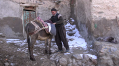 A man saddles a donkey used for transportation in small village in Iran Stock Footage
