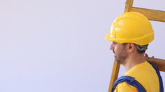 Stock Video Footage of Handsome young bearded workman in a yellow hardhat holding a ladder