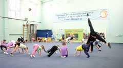 Acrobatic training with istructor in urban children and youth sports center Stock Footage