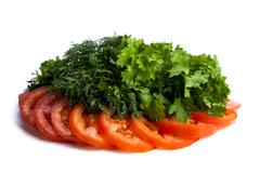Cut pieces of tomatoes and dill and parsley Stock Photos