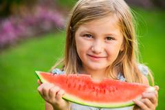adorable blonde girl eating watermelon outdoors - stock photo