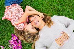 mother and daughter lying together outside on grass - stock photo