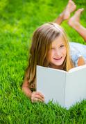 Adorable cute little girl reading book Stock Photos