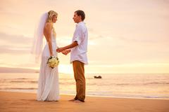 Just married couple holding hands on the beach at sunset Stock Photos