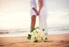 Just married couple holding hands on the beach Stock Photos
