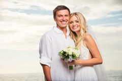 Just married couple on beach at sunset Stock Photos