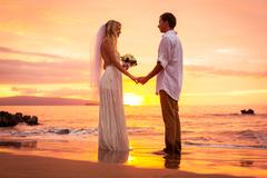 Just married couple on tropical beach at sunset Stock Photos