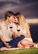 Couple drinking glass of wine on romantic sunset picnic Stock Photos