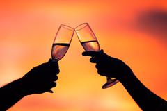 silhouette of couple drinking champagne at sunset - stock photo