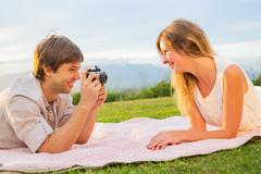 couple taking photos of each other with retro vintage camera on picnic - stock photo