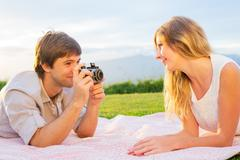 Couple taking photos of each other with retro vintage camera on picnic Stock Photos