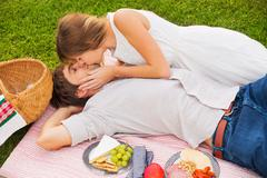 attractive couple on romantic afternoon picnic kissing - stock photo