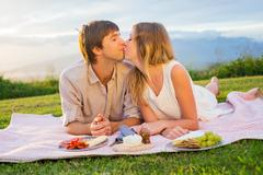 attractive couple kissing on romantic picnic - stock photo