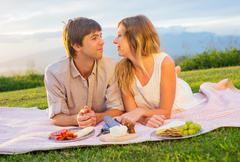 attractive couple on romantic sunset picnic - stock photo