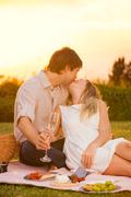 Attractive couple kissing on romantic picnic Stock Photos