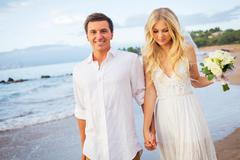 Just married couple walking on the beach at sunset Stock Photos