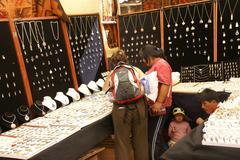young women choosing inca silver jewelry - stock photo