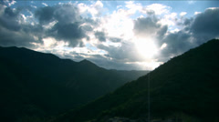 Moving clouds over Hills and sunrays Stock Footage