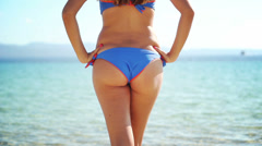 Young woman in a blue and orange bikini slowly walking towards the water Stock Footage