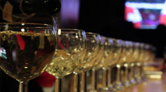 Celebration match. White wine pouring in many glasses. Stock Footage
