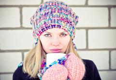 young beautiful woman drinking hot coffee wearing winter knitted hat and mitt - stock photo