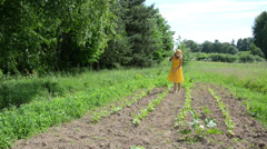 Barefoot farmer girl in dress and hat grub weed in farm Stock Footage