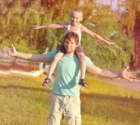 family father man and son boy sitting on shoulders playing outdoor park happi - stock photo